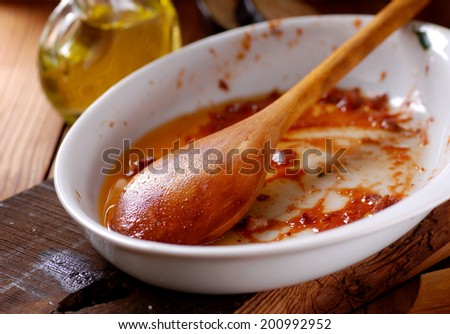 dirty dish with a wooden spoon and kitchen scraps - stock photo