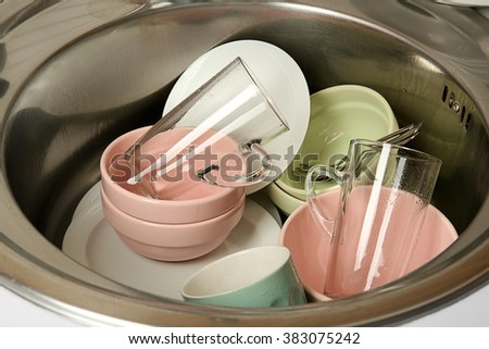 Dirty dishes in kitchen sink closeup - stock photo