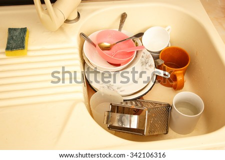 Dirty dishes in kitchen sink in closeup - stock photo