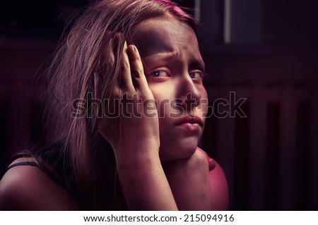 Dirty frightened teenage girl sits locked in a dark room - stock photo