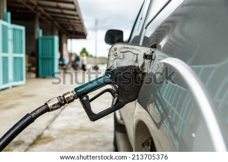 dirty gas pump nozzle in the fuel tank of a pick-up truck - stock photo