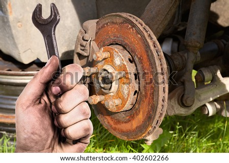 Dirty hand holding wrench. Mechanic is repairing the brakes on a passenger car. - stock photo