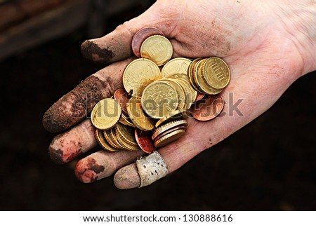 Dirty hand with coins. Small depth of field. - stock photo
