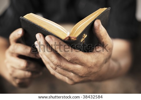 Dirty hands holding an old bible. Very short depth-of-field - stock photo