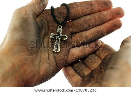 Dirty hands holding cross on white background - stock photo