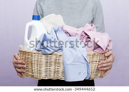 dirty laundry in a wicker basket holding in hands - stock photo