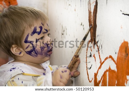 Dirty little boy sketching paintbrush.