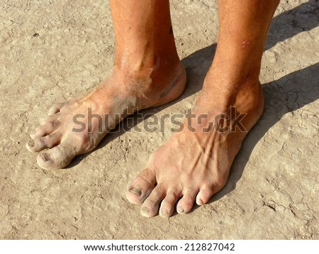 dirty male feet on dried earth - stock photo