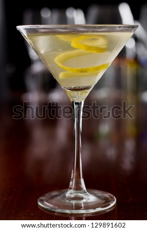 dirty martini chilled and served on a busy bar top with a shallow depth of field and color lights and glasses in the background garnished with a lemon twist - stock photo