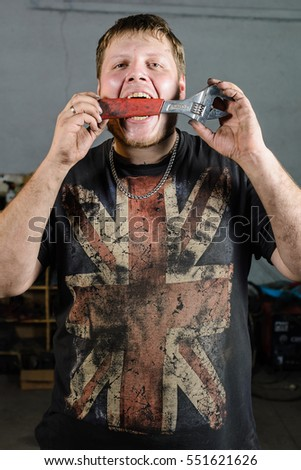 dirty mechanic in a T-shirt with the British flag and with an adjustable wrench in hand