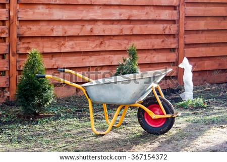 dirty metal garden wheelbarrow on the bare ground