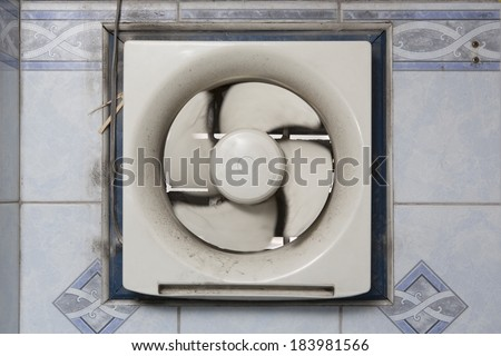 Dirty oil stained kitchen exhaust fan on a mosaic wall. - stock photo