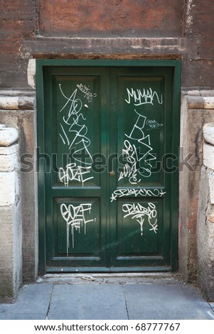 dirty, old, green, wooden doors, many white graffiti on doors - stock photo