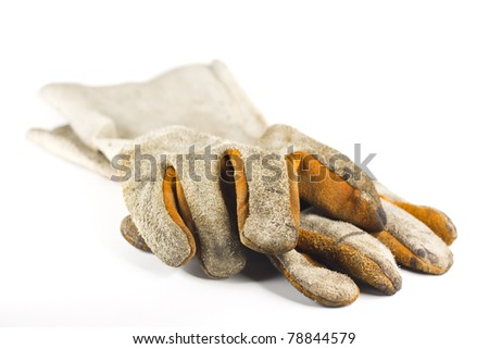 Dirty old leather gloves  shallow focus isolated on white background - stock photo