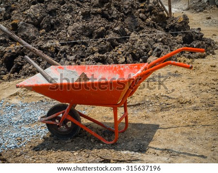 dirty orange wheelbarrow with  hoe