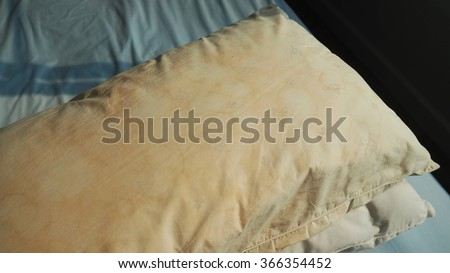 Dirty pillow from saliva stain on the bed. Dirty pillow with pale yellow and brown color. - stock photo