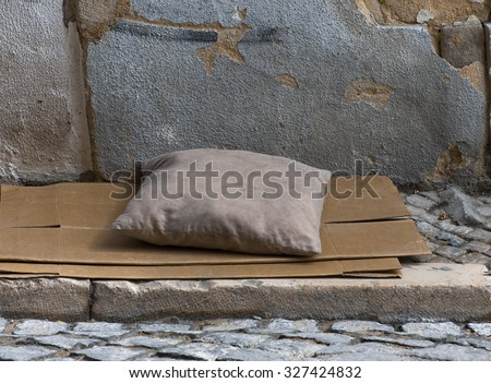dirty pillow on a paper-box matrass in the street of Lisbon - stock photo