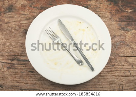 Dirty plate and cutlery on a wood table