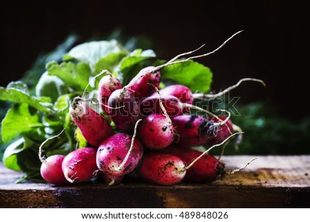Dirty radish, vintage wooden background, selective focus