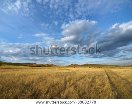 Dirty road over yellow hills - stock photo