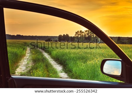 Dirty rural road in spring summer  field, meadow, countryside. View from car window. Freedom and dream concept. - stock photo