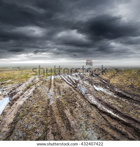 Dirty rural road with puddles and mud under dark dramatic stormy sky, SUV car goes far away, transportation background