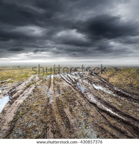 Dirty rural road with puddles and mud under dark dramatic stormy sky, transportation background