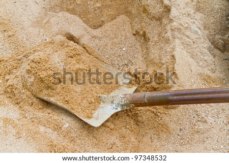 dirty shovel working on sand - stock photo
