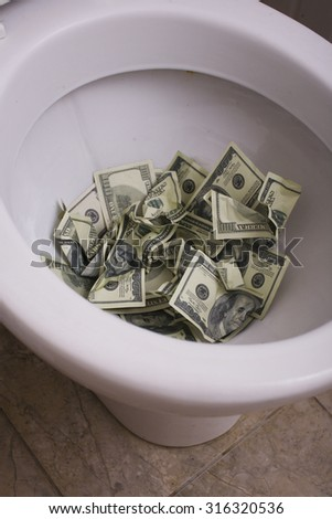 dirty toilet with money close up, lot of cash useless taxes - stock photo