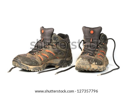 dirty trekking boots over white background. - stock photo