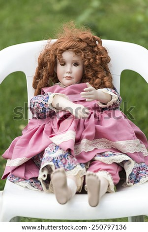 Dirty untidy Porcelain doll sitting on a plastic chair outdoors  - stock photo