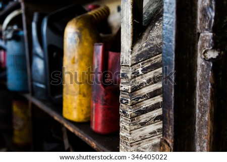 Dirty used engine oil bottles in a auto repair garage. Soft focus. Shadows. Noise - stock photo