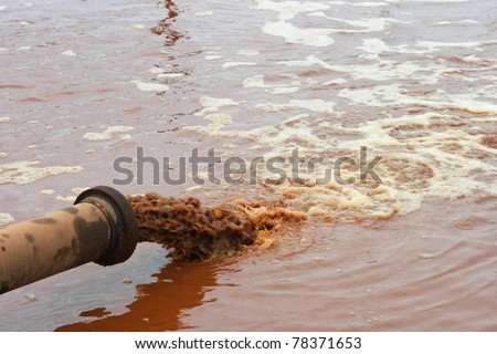 Dirty water discharged into river - stock photo
