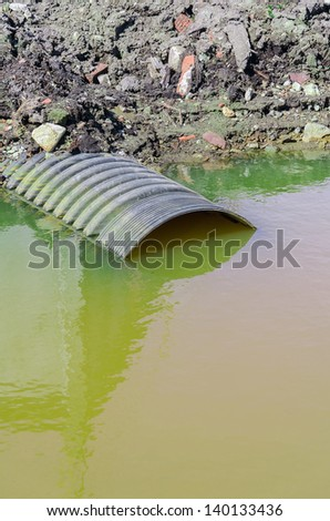 Dirty water stems from the pipe - stock photo