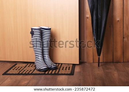 Dirty wellington boots with umbrella on door mat in room - stock photo