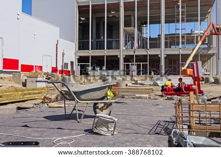 Dirty wheelbarrow are standing at construction site, workers and machines in background. - stock photo