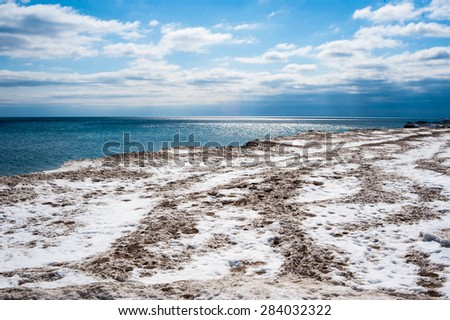 Dirty white and brown ice and snow coastline against bright partly cloudy blue sky and dark blue water horizon. - stock photo