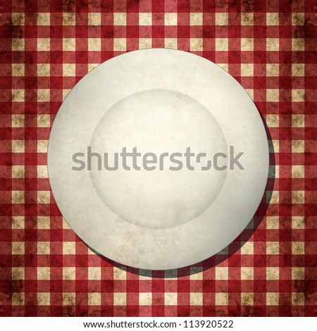 Dirty white empty plate on red and white checkered tablecloth, top view