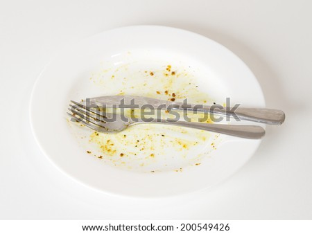 Dirty white plate and knife and fork on white kitchen table - stock photo