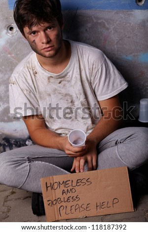 Dirty young homeless and jobless guy asking for help sitting on a street - stock photo