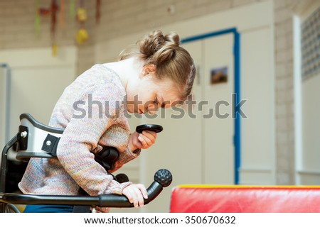 Disability a disabled child in a walking aid exploring her surroundings / disability a disabled child exploring her surroundings - stock photo