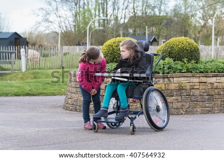 Disability a disabled child in a wheelchair with her younger sister together relaxing outside / Disability a disabled person relaxing outside