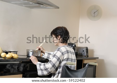 Disabled adult woman in wheelchair cooking dinner - stock photo
