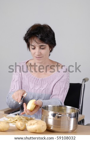 disabled adult woman in wheelchair peeling potatoes - stock photo