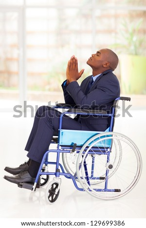 disabled african businessman sitting on wheelchair and praying - stock photo