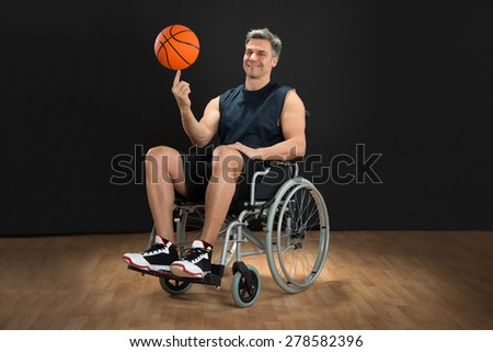 Disabled Basketball Player On Wheelchair Spinning Ball On His Finger - stock photo