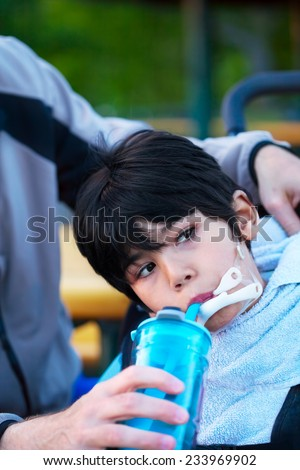 Disabled biracial little boy in wheelchair drinking water from sippy cup - stock photo