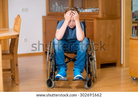 disabled boy in wheelchair at home is sad - stock photo