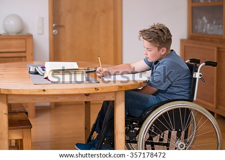 disabled boy in wheelchair doing homework - stock photo