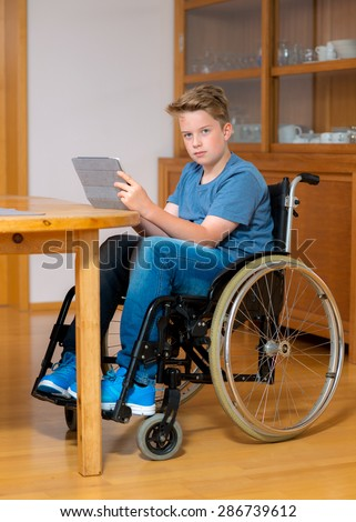 disabled boy in wheelchair doing homework and chatting in the internet - stock photo